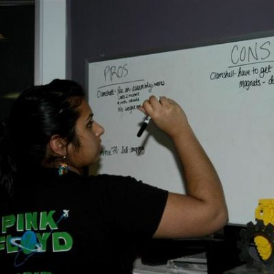 Meera N. recording the pros and cons from the minibot design discussion.