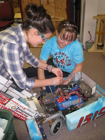 Linsay F. and Lizzie P. taking control systems compnents off of an old robot.