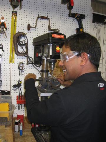 Mr. Nair using the drill press.