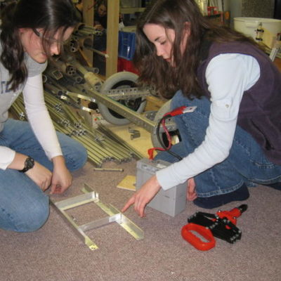 Brittany F. helping Carissa F. with the battery box.