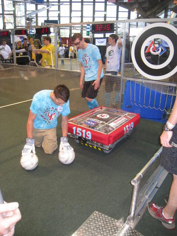 Tim P. placing balls in front of the robot before a match.