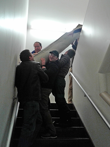 Carrying practice field carpet up stairs at Cirtronics.